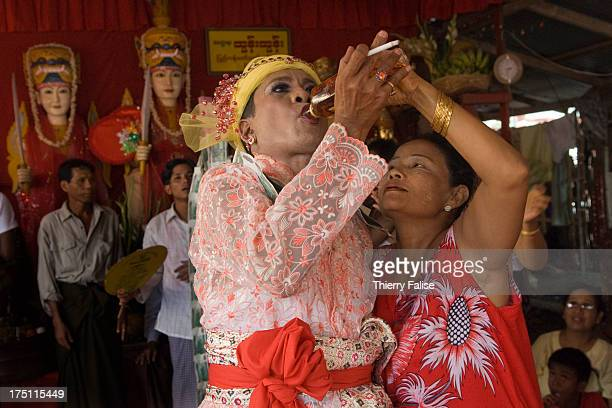 A medium shares a bottle of whisky with a female reveller during a dance in one of the numerous shrines dedicated to the nats during the Taungbyon...