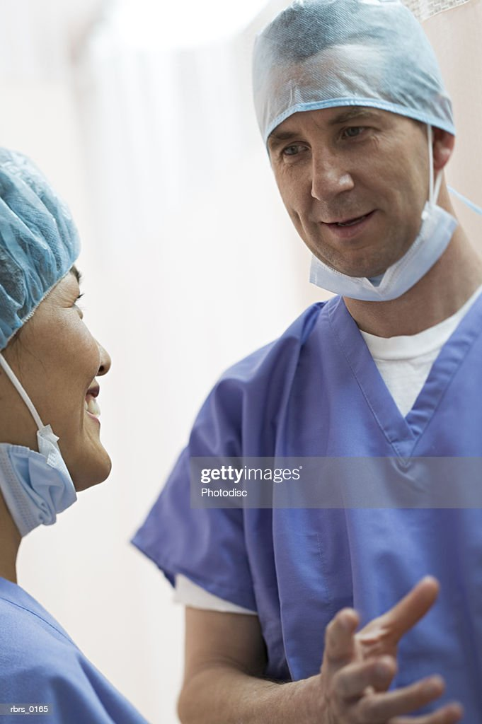 medium shot as two adult medical doctors converse back and forth : Foto de stock