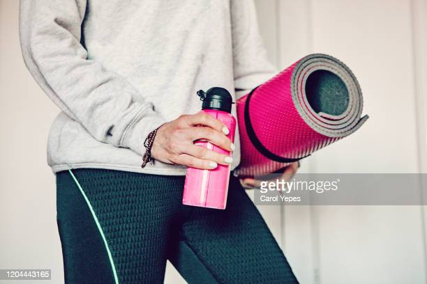medium  shot mature woman with reusable water bottle and exercise mat - mat stock pictures, royalty-free photos & images