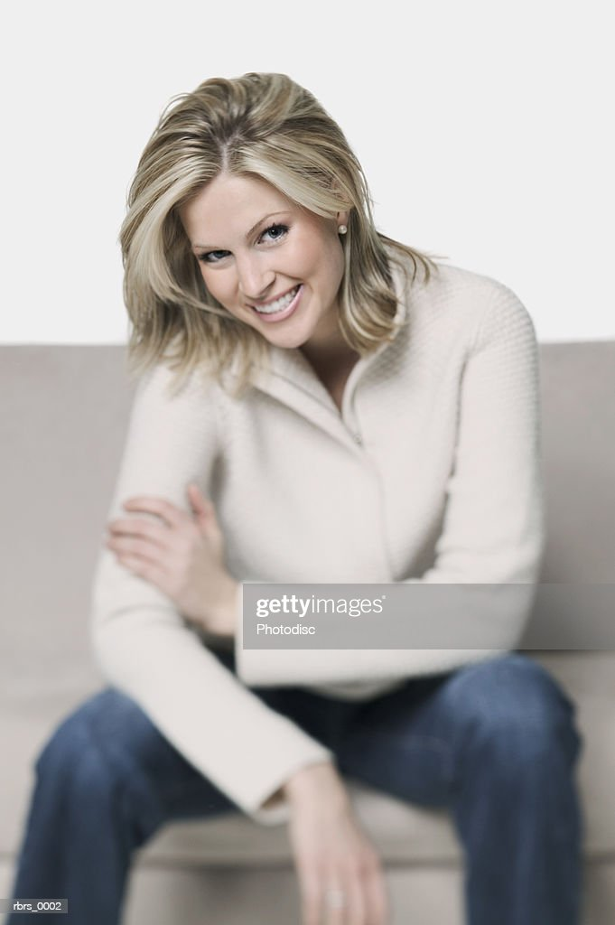 medium shot of a blonde young adult woman as she sits on a couch and smiles : Foto de stock