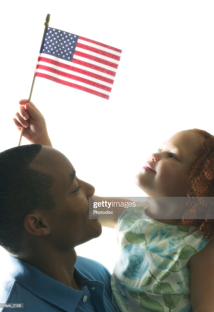 medium shot of a father and daughter as the girl waves an american flag : Stockfoto