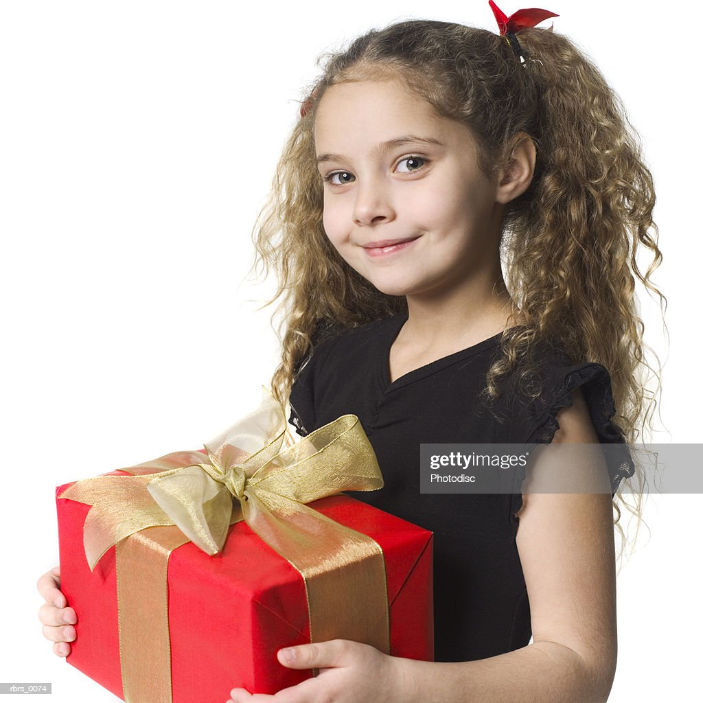 medium shot of a female child as she hold up a red christmas present and smiles : Foto de stock