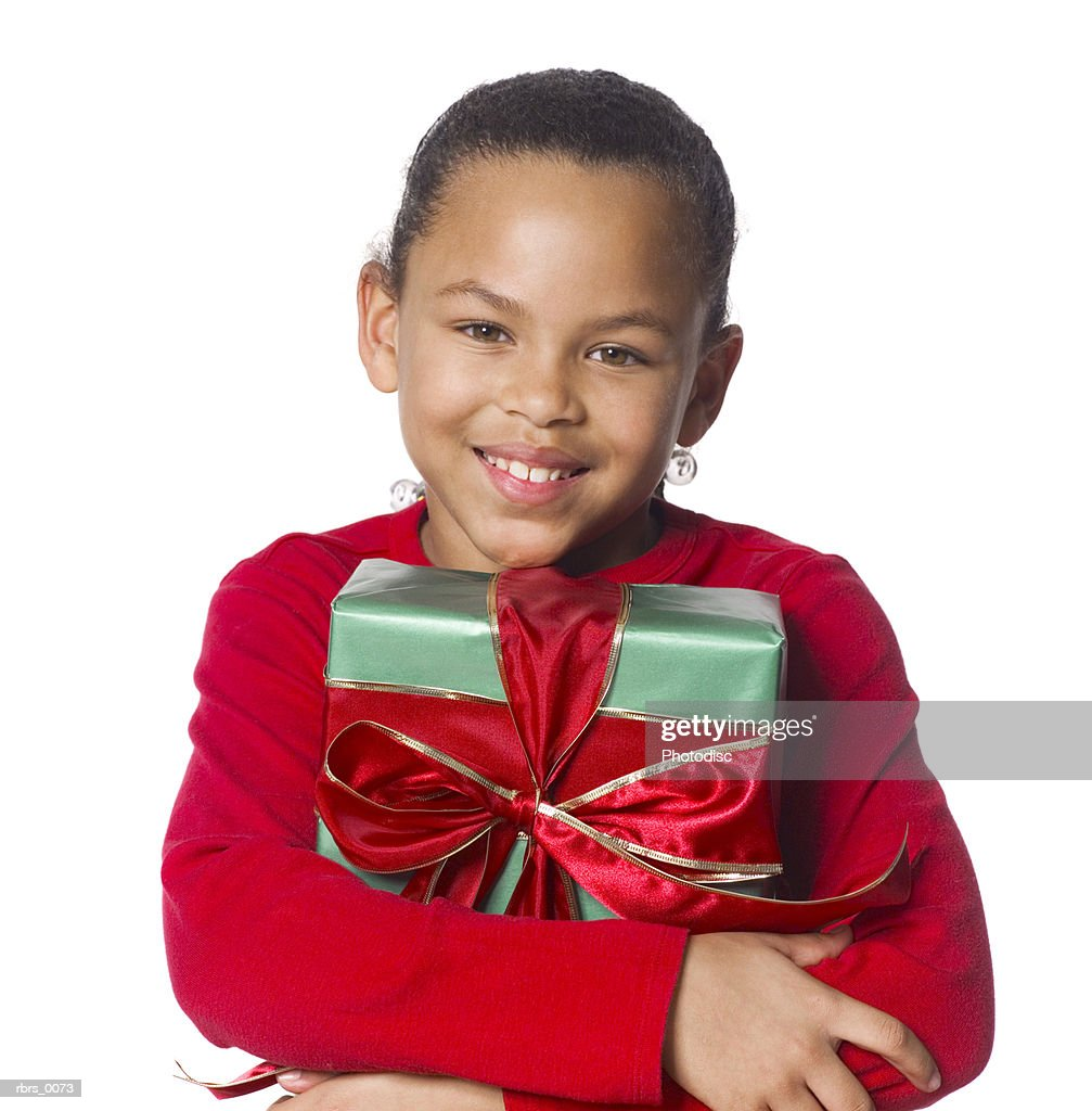 medium shot of a female child dressed in red as she wraps her hands around a gift : Foto de stock