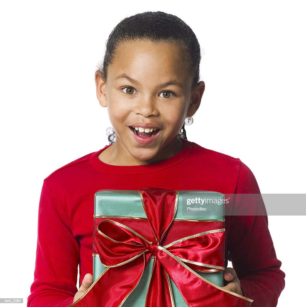 medium shot of a female child in a red shirt as she holds a wrapped present : Stockfoto