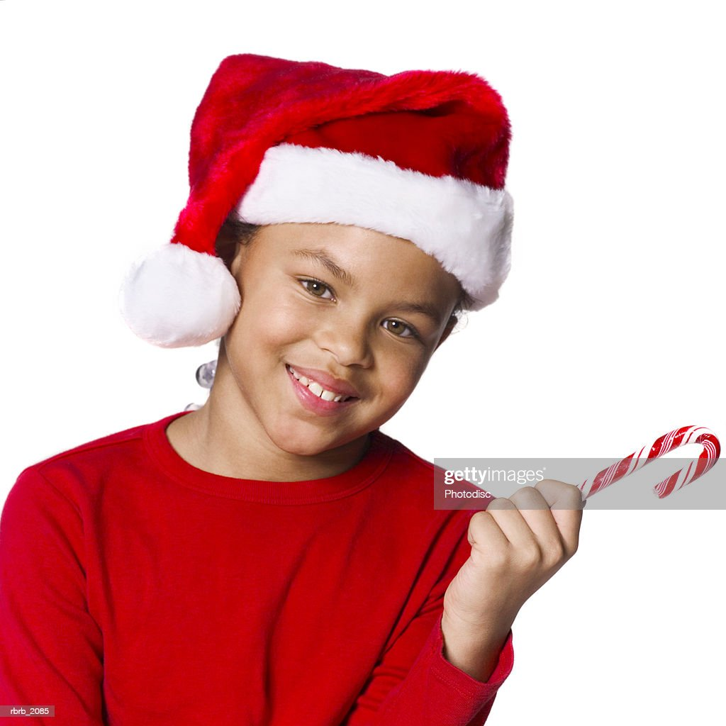 medium shot of a female child in a santa hat as she holds out a candy cane : Stockfoto