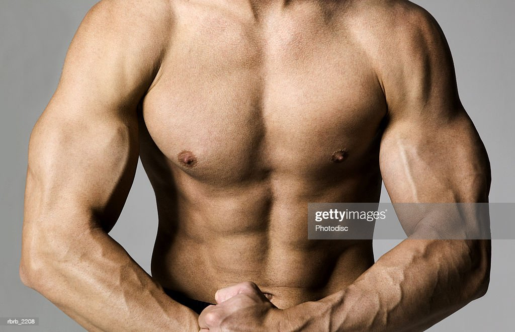 medium shot of a fit male bodybuilder as he flexes his muscles : Stock Photo