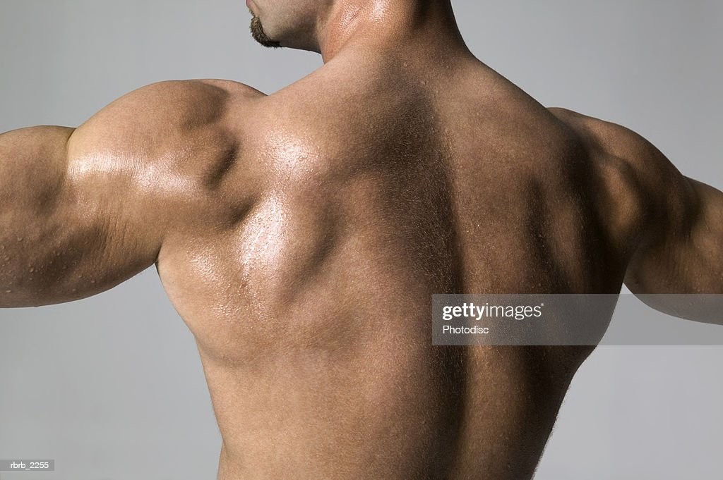 medium shot of a male bodybuilder as he flexes his back muscles : Foto de stock