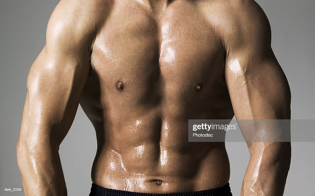 medium shot of a male bodybuilder as he flexes his stomach muscles : Stock Photo