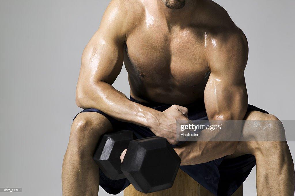 medium shot of a male bodybuilder as he lifts a weight : Foto de stock