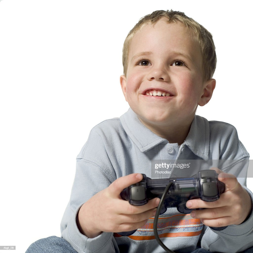 medium shot of a male child as he smiles while using a video game controler : Stockfoto