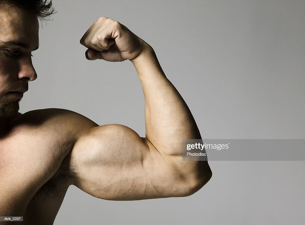 medium shot of a muscular male as he flexes his bicep : Foto de stock