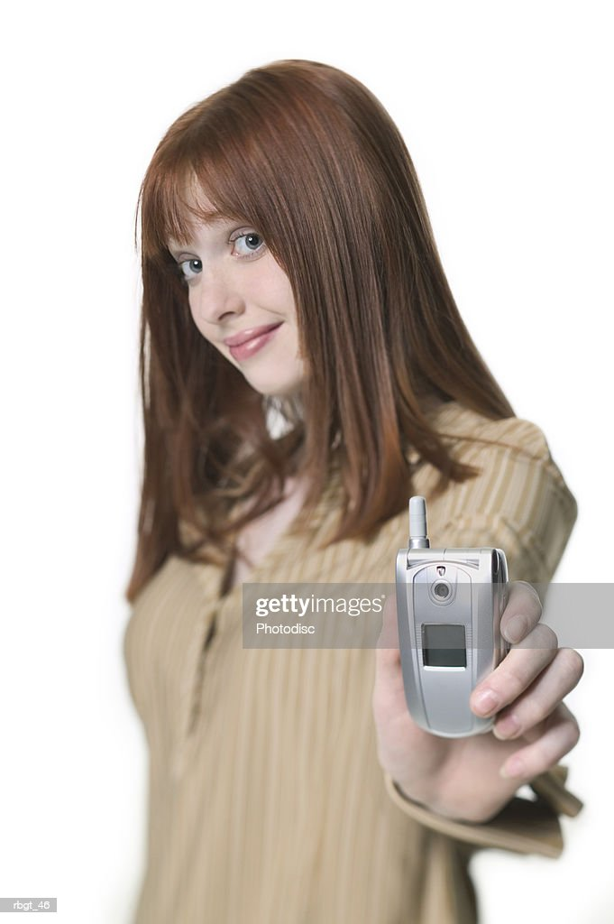 medium shot of a teenage female as she holds out a small cell phone : Stockfoto