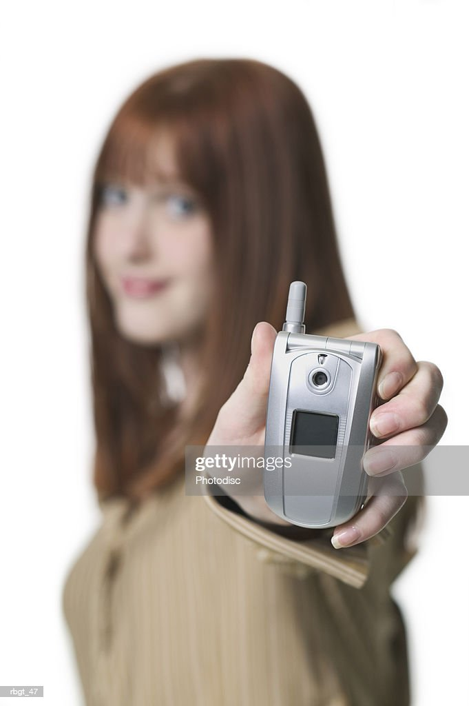 medium shot of a teenage female as she holds out a small cell phone to the camera : Stockfoto