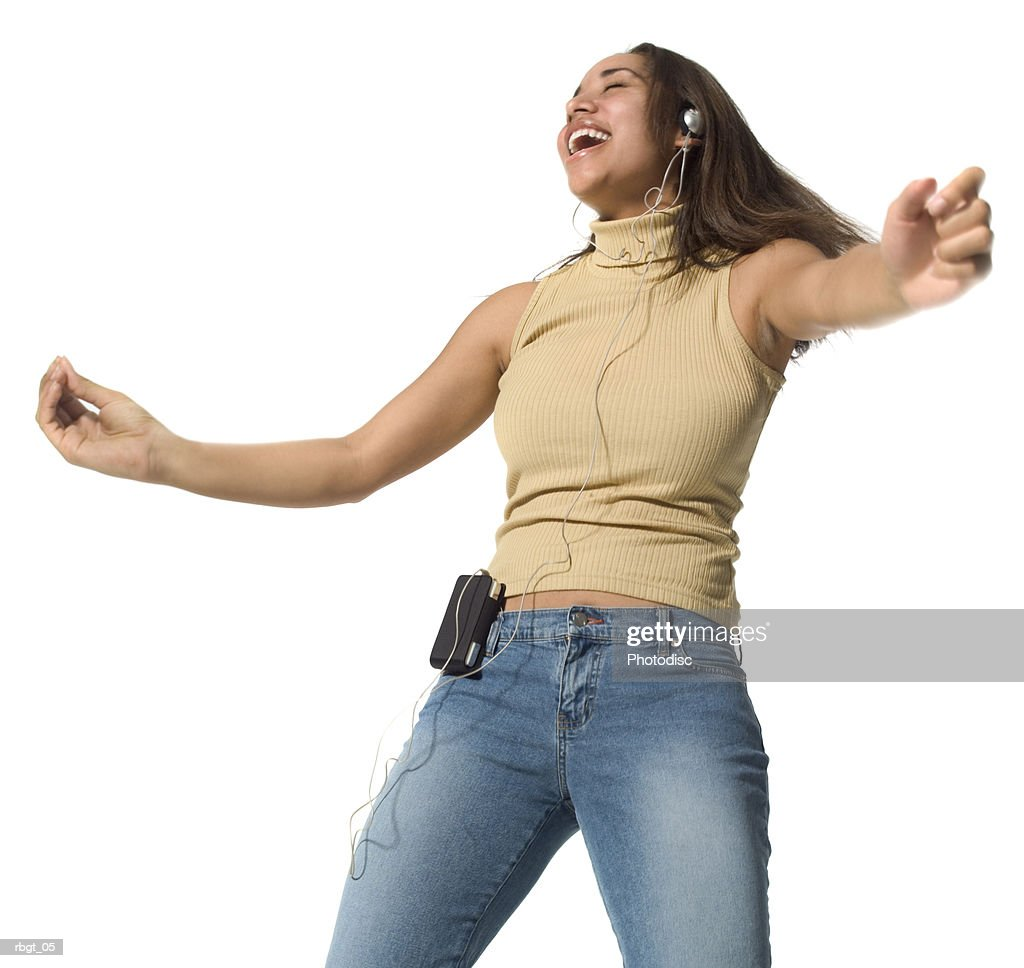 medium shot of a teenage female as she listens to music over headphones and dances : Stockfoto