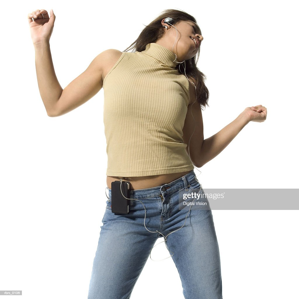 medium shot of a teenage girl as she dances while listening to headphones : Foto de stock