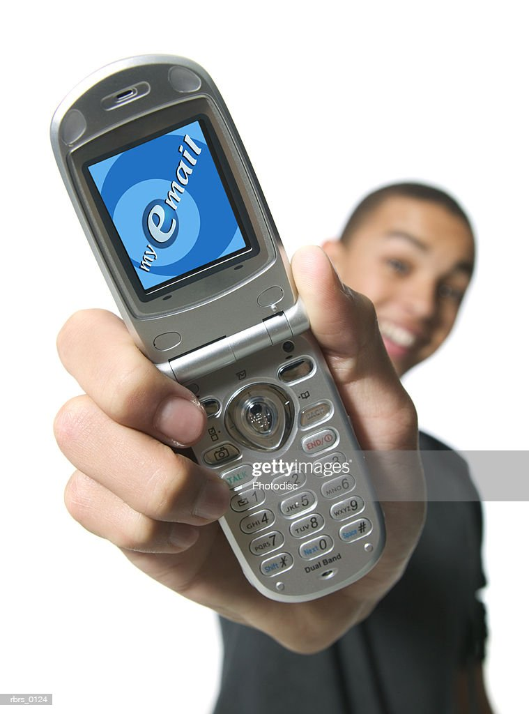 medium shot of a teenage male as he displays his viewscreen on his cell phone : Foto de stock