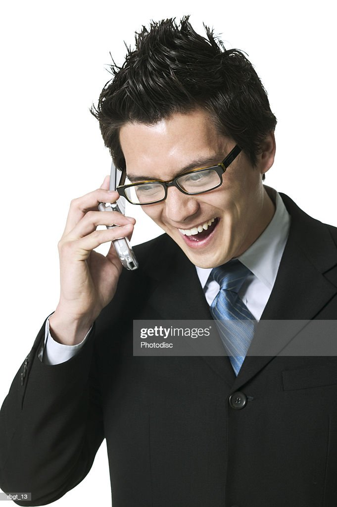 medium shot of a young adult business man as he laughs and talks on his cell phone : Stockfoto