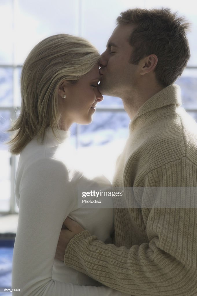 medium shot of a young adult couple as the man kisses the forehead of the woman : Stockfoto