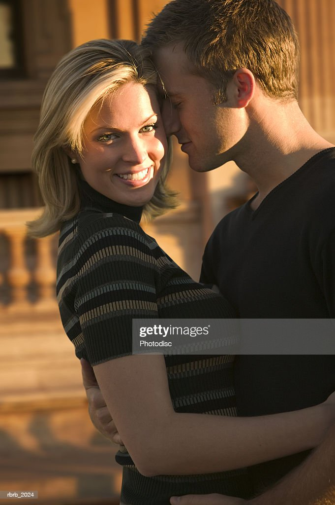 medium shot of a young adult couple as the man leans in and kisses the cheek of the woman : Stockfoto