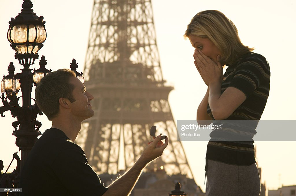 medium shot of a young adult couple as the man proposes in front of the eiffel tower in paris : Foto de stock