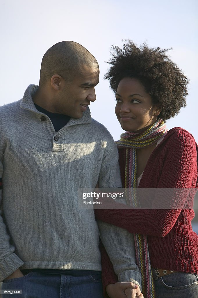 medium shot of a young adult couple as the woman hangs on to the mans arm : Stockfoto