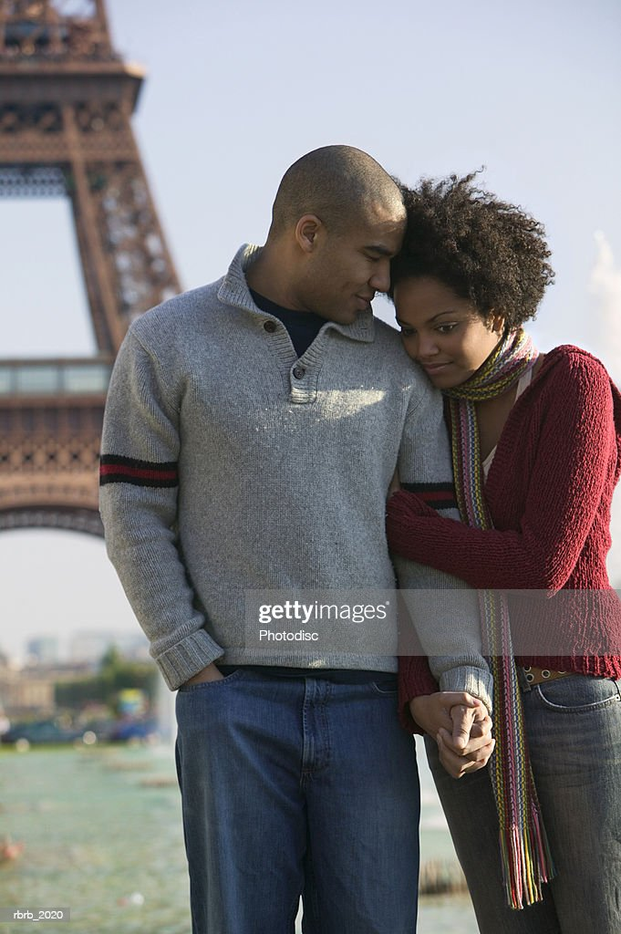 medium shot of a young adult couple as the woman holds the mans arm while sightseeing in paris : Stockfoto