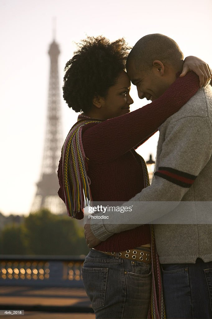medium shot of a young adult couple as they embrace at the eiffel tower in paris : Stockfoto