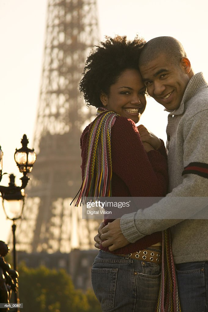 medium shot of a young adult couple as they embrace at the eiffel tower in paris and smile at the camera : Foto de stock