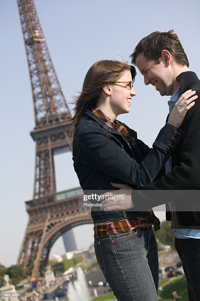 medium shot of a young adult couple as they embrace at the eiffel tower in paris : Foto de stock