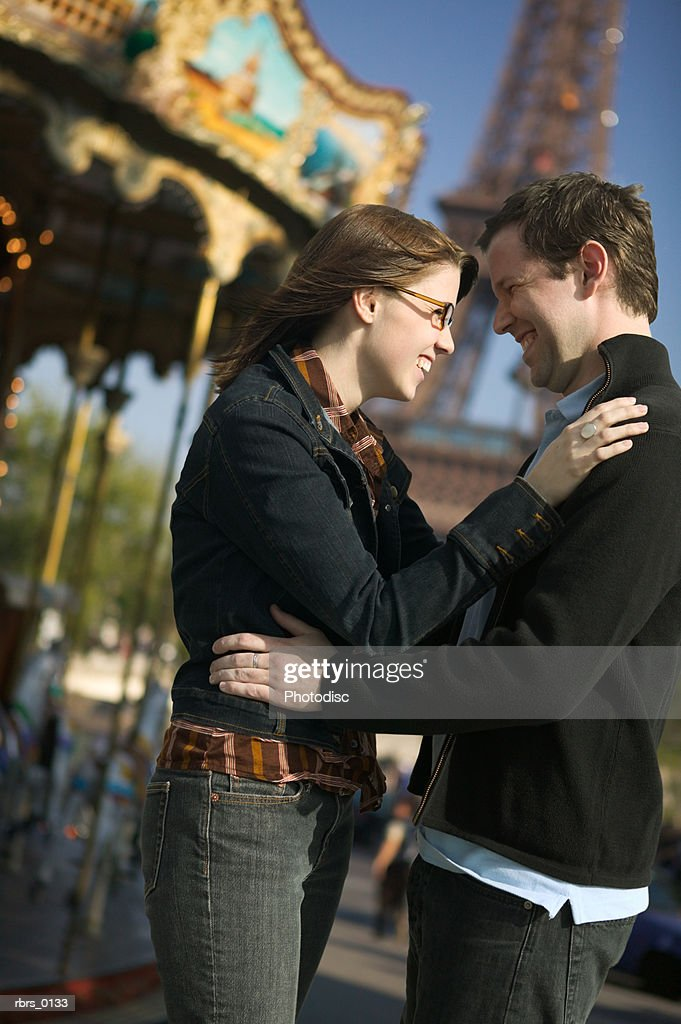 medium shot of a young adult couple as they embrace near a carousel in paris : Foto de stock