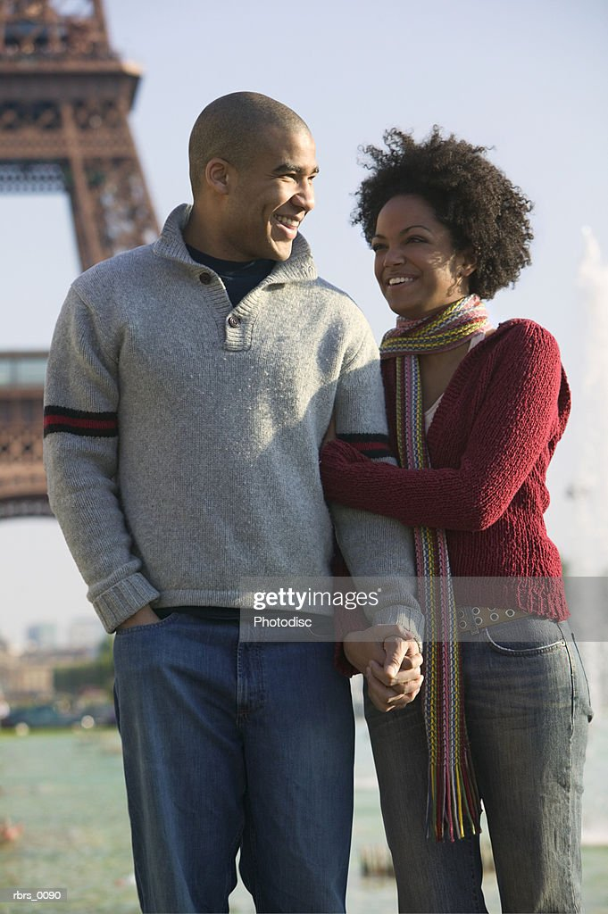 medium shot of a young adult couple as they hold hands at the eiffel tower in paris : Foto de stock
