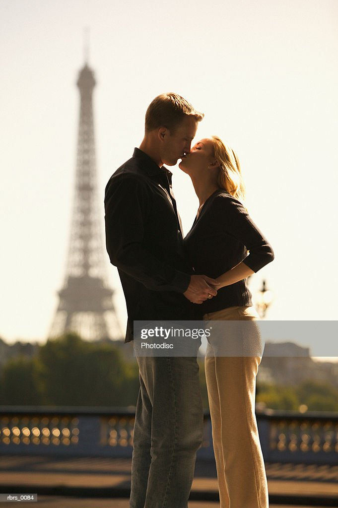 medium shot of a young adult couple as they lovingly embrace at the eiffel tower in paris : Foto de stock