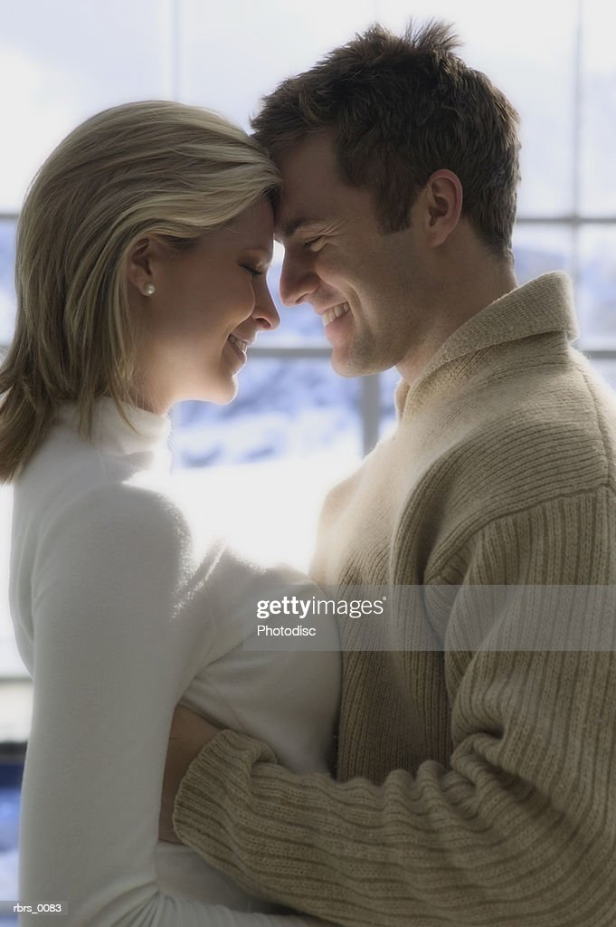 medium shot of a young adult couple as they lovingly embrace : Foto de stock