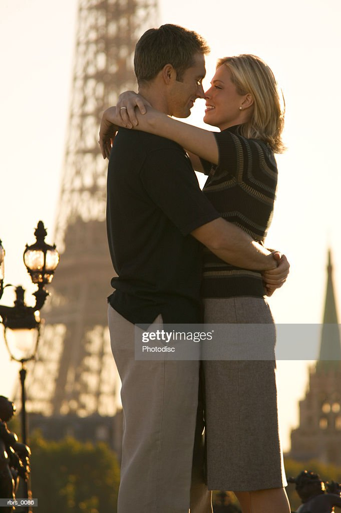 medium shot of a young adult couple as they lovingly hug at the eiffel tower in paris : Foto de stock