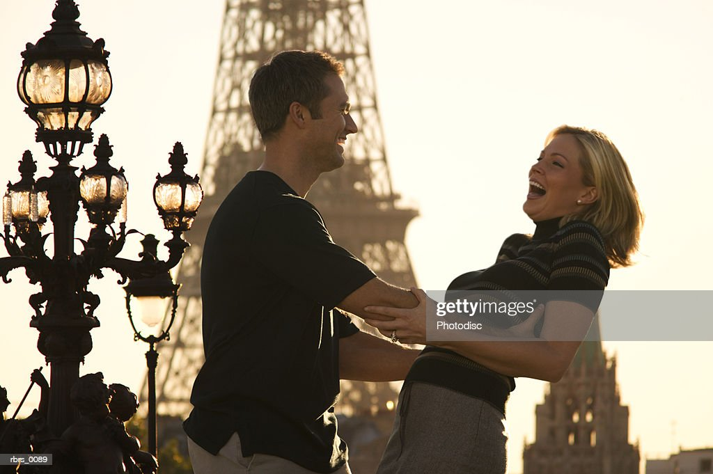 medium shot of a young adult couple as they lovingly play around at the eiffel tower in paris : Foto de stock