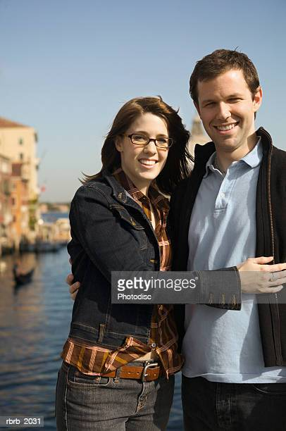 medium shot of a young adult couple as they pose near the grand canal in venice italy