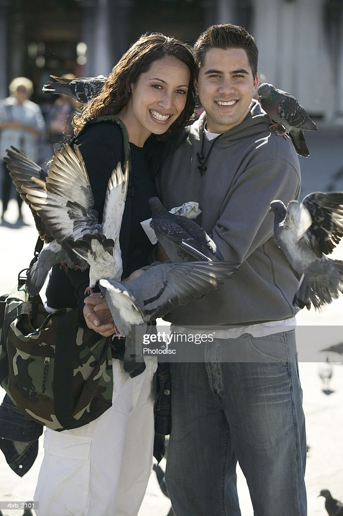 medium shot of a young adult couple as they smile while surrounded by birds : Stockfoto