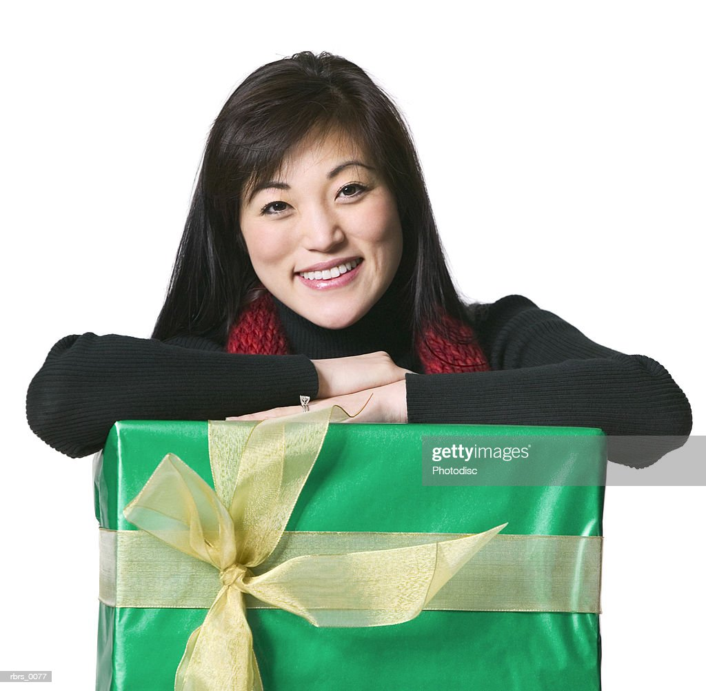 medium shot of a young adult female as she leans over a large christmas gift : Foto de stock