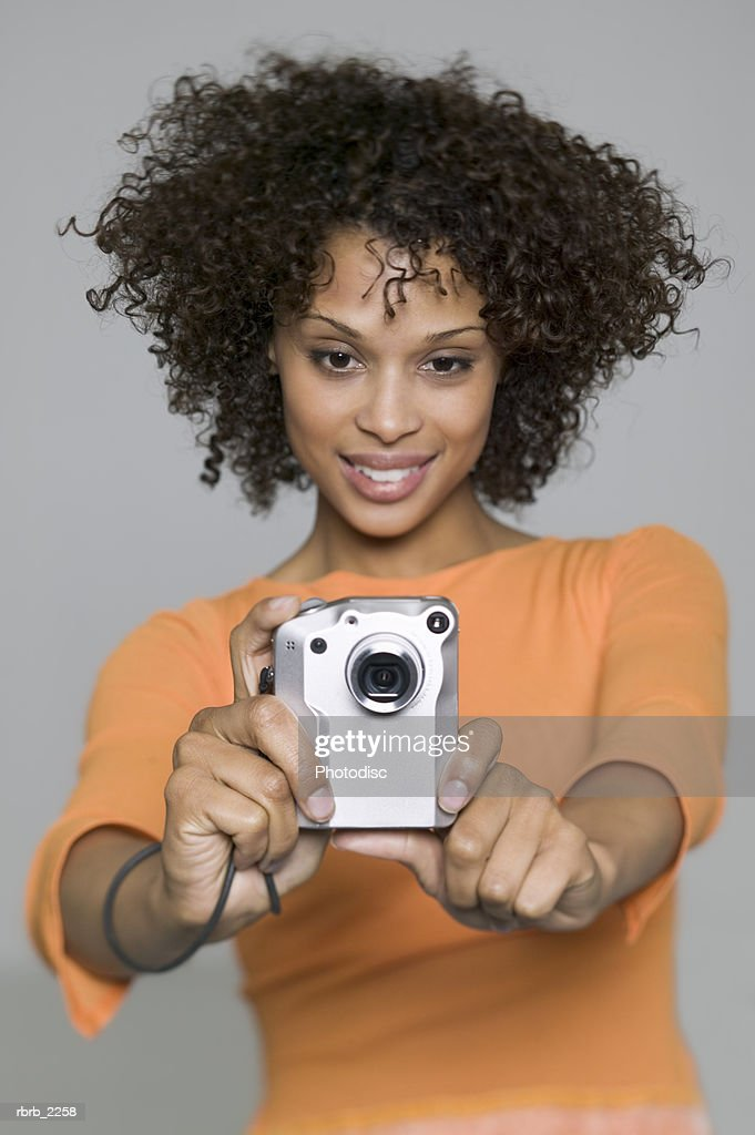 medium shot of a young adult female as she uses her digital camera : Foto de stock