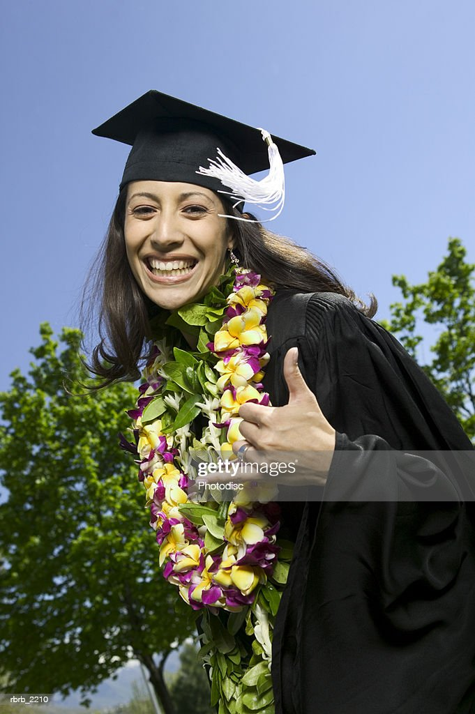 medium shot of a young adult female college graduate with a floral lei as she celebrates : Foto de stock