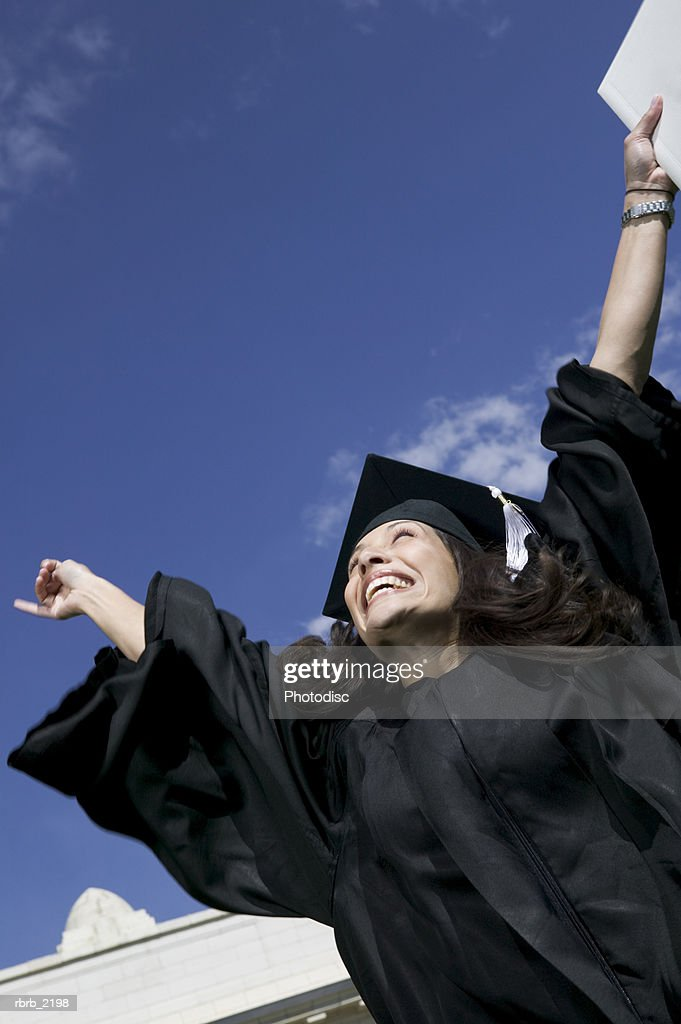 medium shot of a young adult female graduate as she holds up her diploma in celebration : Foto de stock