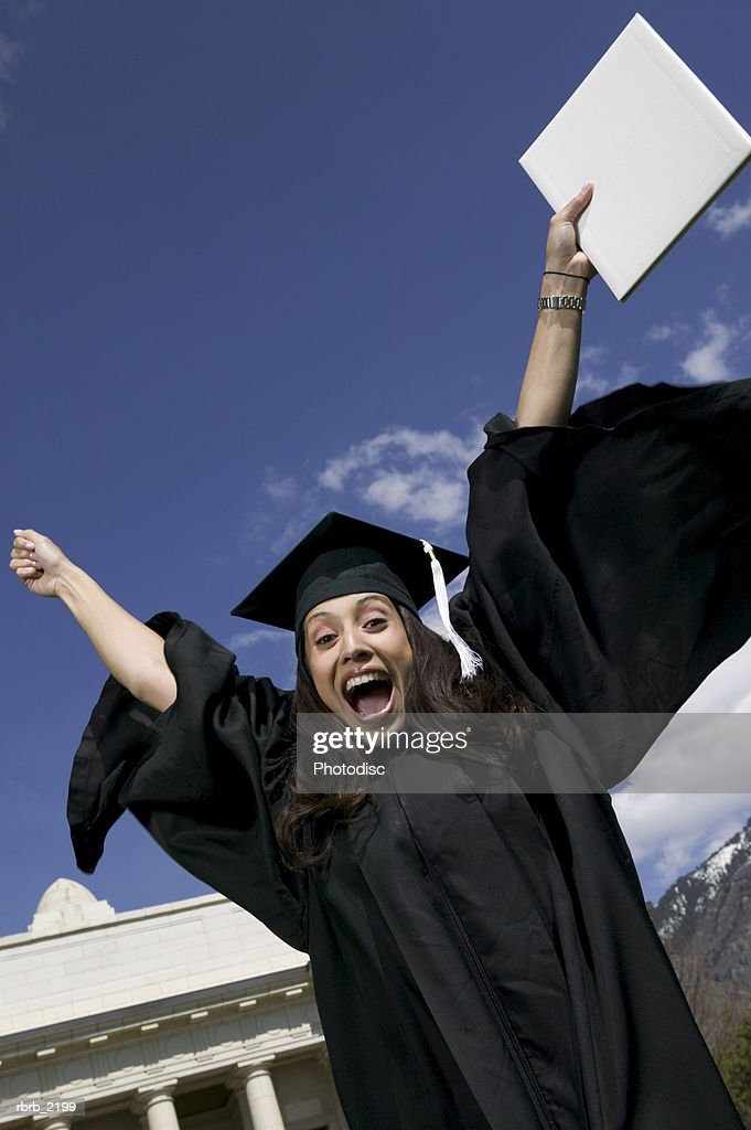 medium shot of a young adult female graduate as she wildly celebrates : Foto de stock