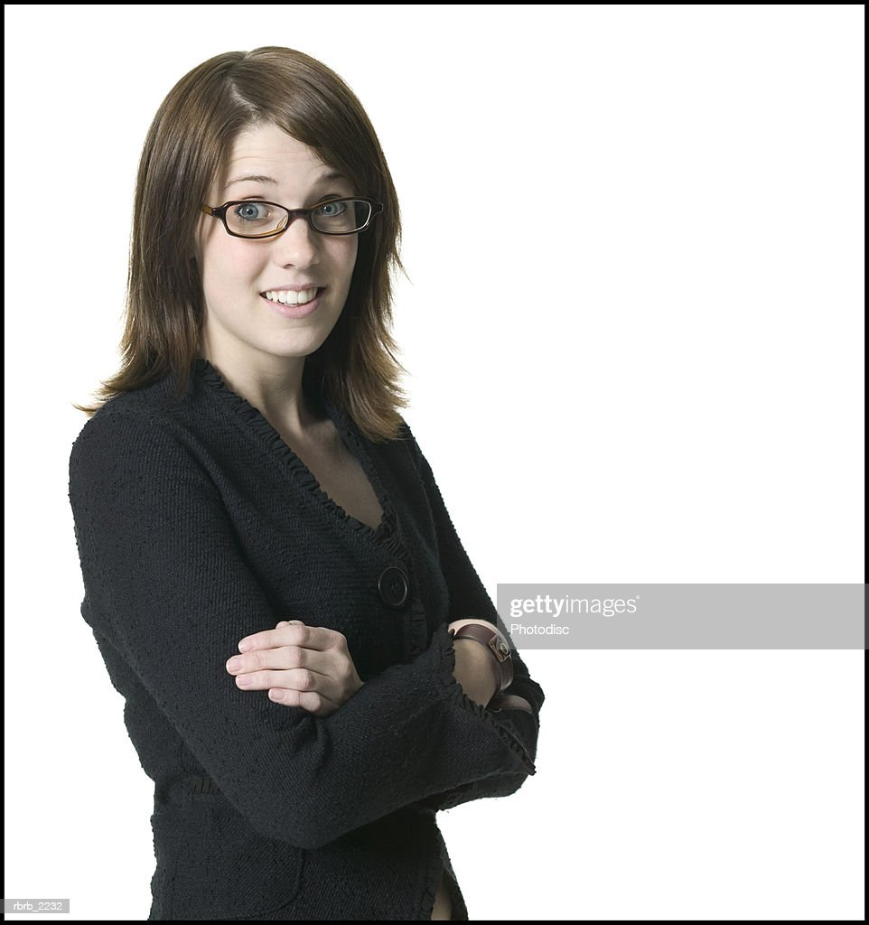 medium shot of a young adult female in a black shirt and glasses as she folds her arms and smiles : Foto de stock