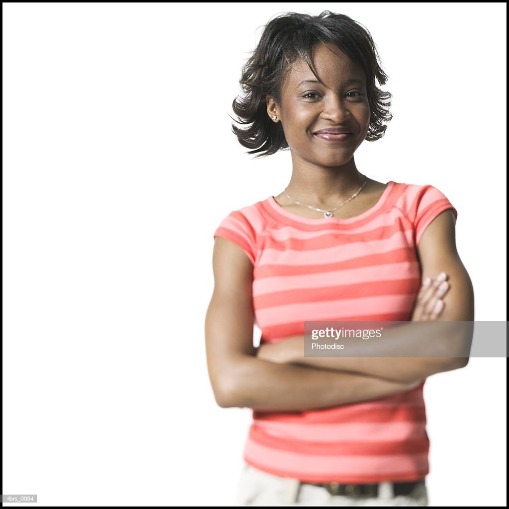 medium shot of a young adult female in a striped shirt as she folds her arms and smiles : Stockfoto