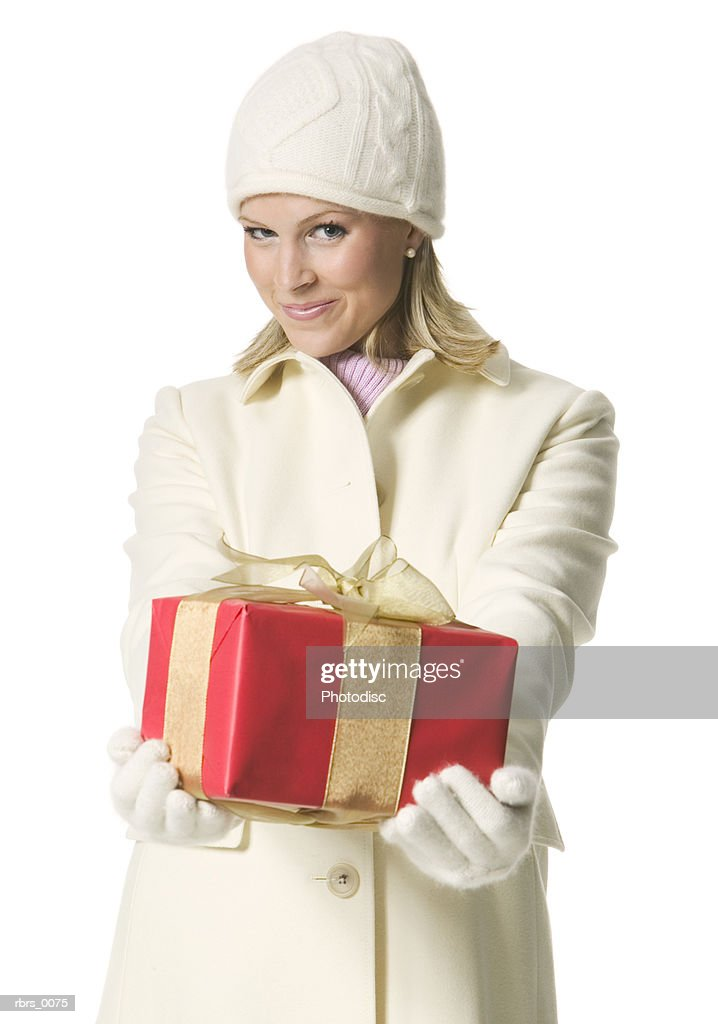 medium shot of a young adult female in a winter coat as she hold up a christmas gift : Foto de stock