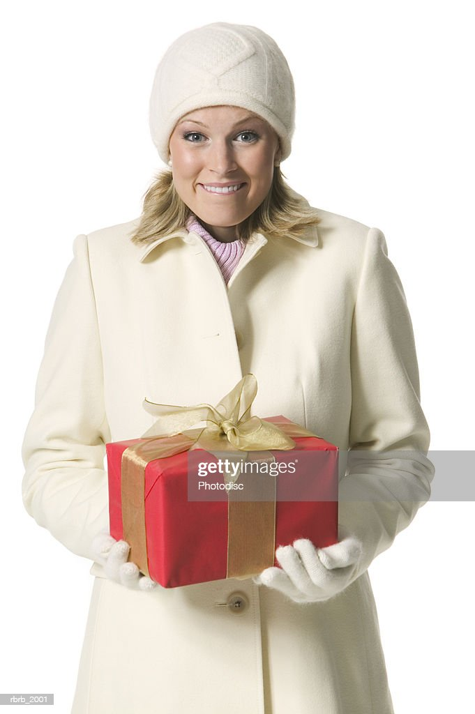 medium shot of a young adult female in a winter hat and coat as she holds a present : Stockfoto