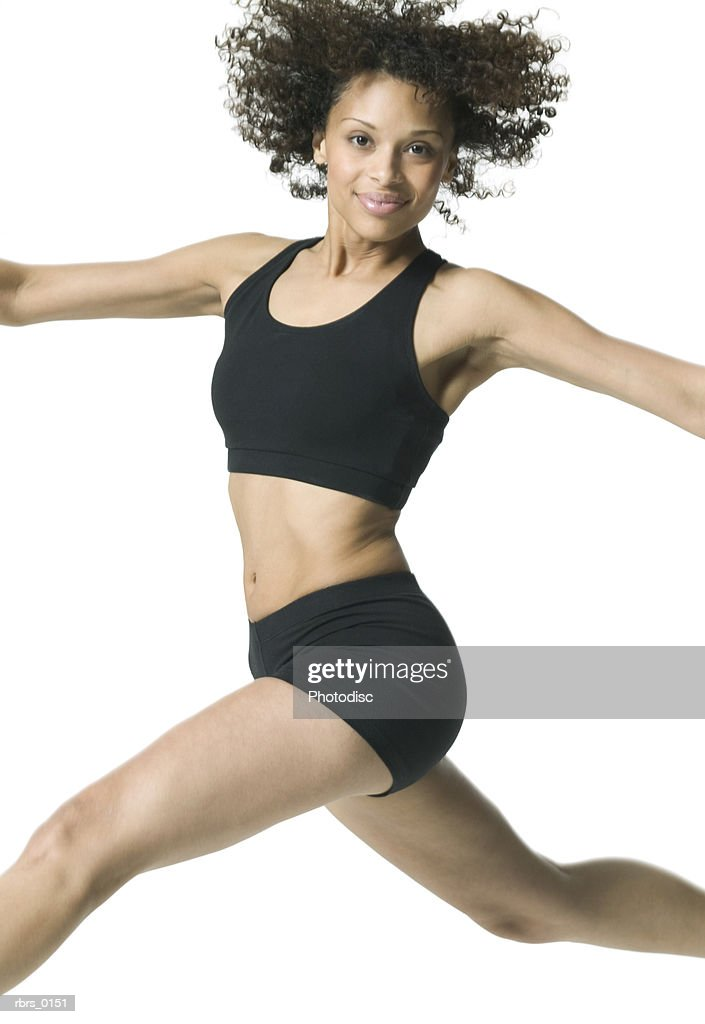medium shot of a young adult female in a workout outfit as she jumps through the air : Foto de stock