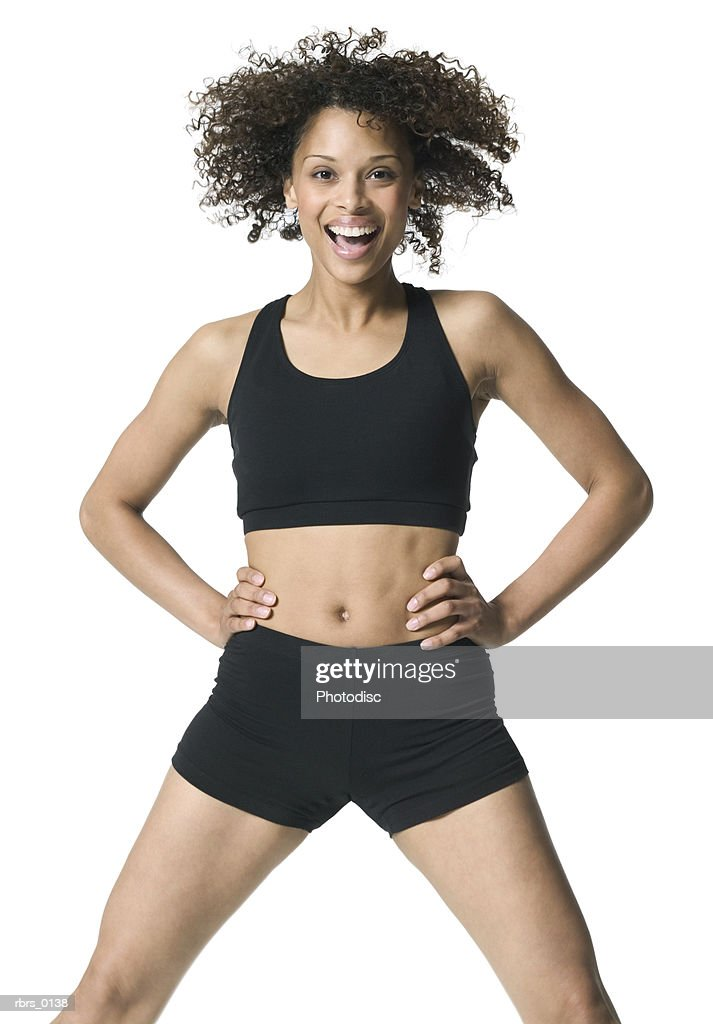 medium shot of a young adult female in a workout outfit as she puts her hand on her hips and smiles : Foto de stock