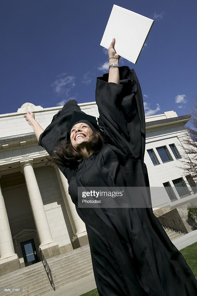 medium shot of a young adult female in her cap and gown as she celebrates her graduation : Stockfoto