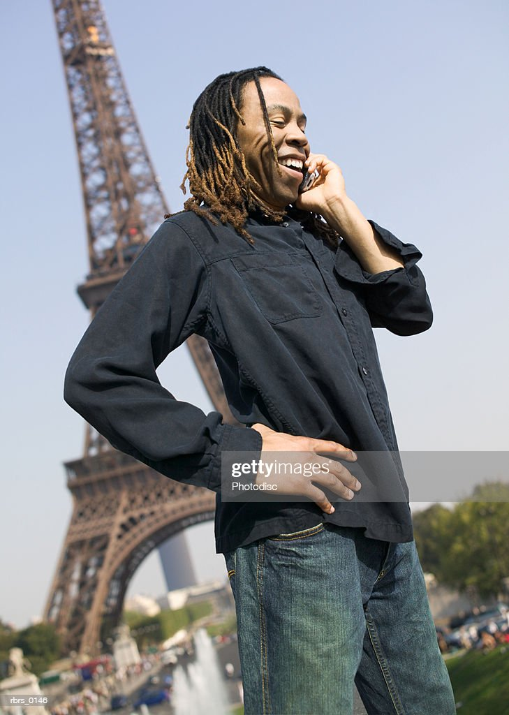 medium shot of a young adult male as he chats on his cell phone while sightseeing in paris : Foto de stock